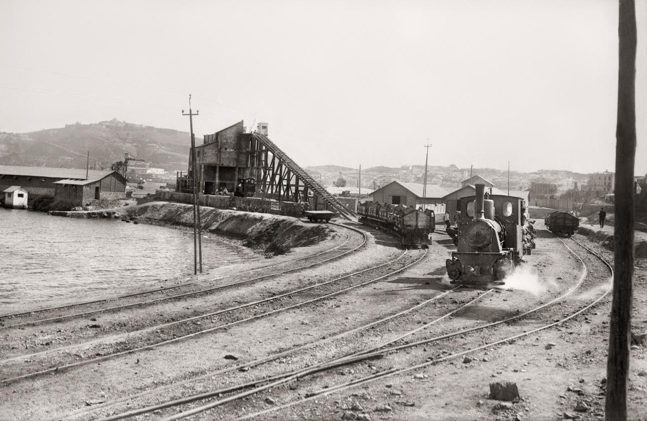 Fabrica de bloques prefabricados y locomotora de transporte de materiales, durante la construcción de los muelles de España y Cañonero Dato. Ceuta, 1925<br/>Gelatina de plata / Silver gelatin